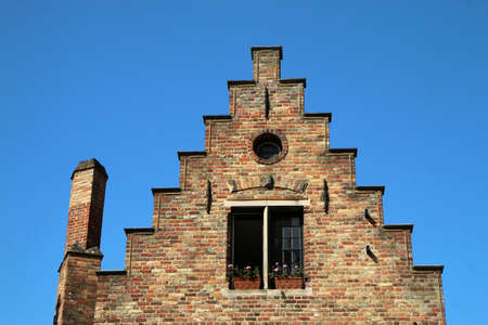 The detail of the terraced brick gable wall of the traditional historic house in Bruges in Belgium. 免版税图像
