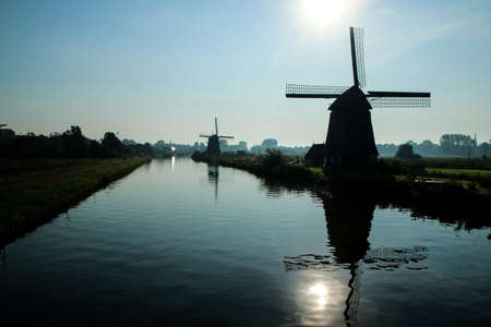 The view from the Dutch countryside by the city of Alkmaar in Netherlands. The canal with the windmills nearby the city. 免版税图像