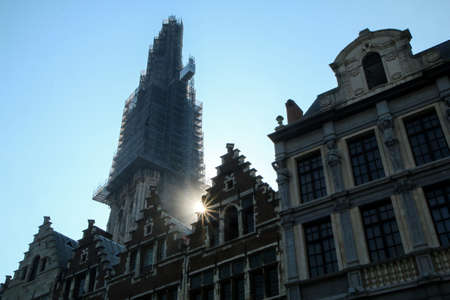 The detail of the old historic houses at the square in Belgian city of Antwerp with a tower of the cathedral under reconstruction.