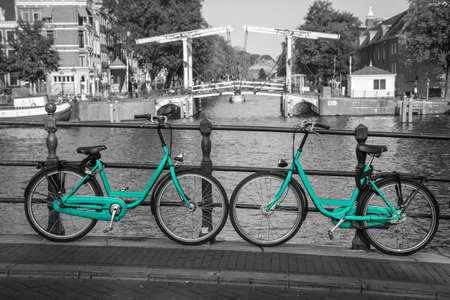 Two fresh azure bikes on the streets of Amsterdam. Symbol for clean and ecological urban transport. Isolated in a black and white background. 免版税图像