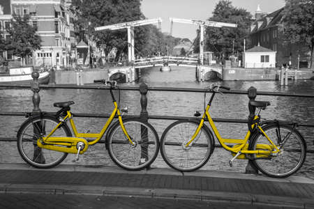A picture of a two yellow bikes on the bridge over the channel in Amsterdam. The background is black and white. 免版税图像