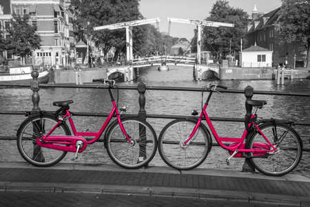 A picture of two pink bikes on the bridge over the channel in Amsterdam. The background is black and white. 免版税图像