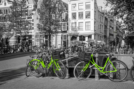 Two fresh green bikes on the streets of Amsterdam. Symbol for clean and ecological urban transport. Isolated in a black and white background. 免版税图像