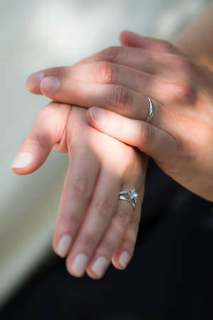 The young couple is holding their hands after the wedding ceremony and showing their new rings symbol for their love.