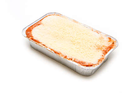 The semifinished lasagne in the aluminium tub isolated on a white background. The fast ready to cook meal. 免版税图像