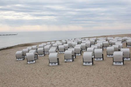 The chairs on the beach by the northern sea are waiting for the visitors. Or the rain comes first? 免版税图像
