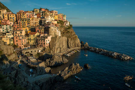 A Picture of the Italian town Manarol during the late summer afternoon. The nice colorful houses are standing on rocks above the sea. 免版税图像