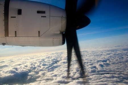 An aerial view from the airplane flying high above the ground. A look from the plane´s window with engine visible. 免版税图像