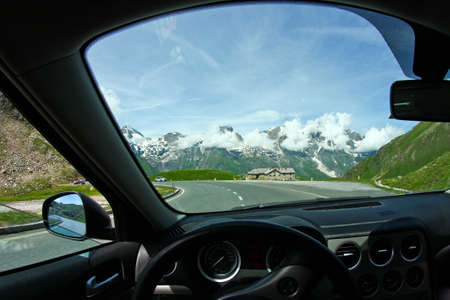 A view on the Alps through the windscreen of the car while driving on the curvy road.