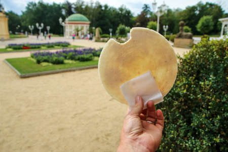 The hand is holding the traditional Czech round spa wafer at the spa city promenade. 免版税图像