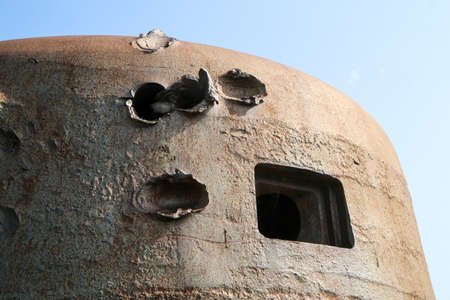 The bullet holes in the armor of the bunker turret from second world war. 免版税图像