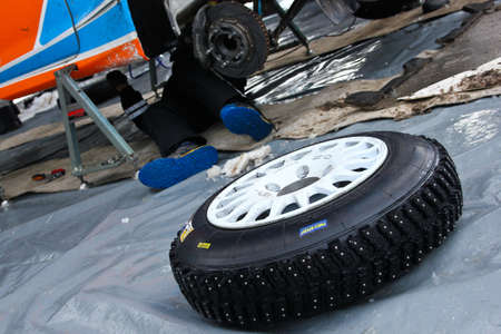 A detail of the tire with studs used for the rally cars to have a better control on snow and ice. Lies in front of the car.