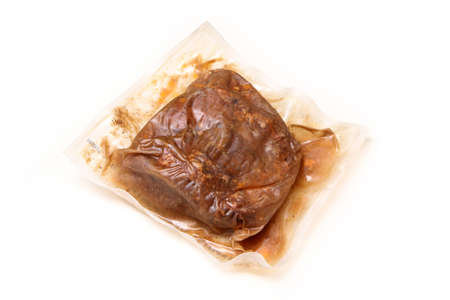 The semifinished pulled pork meat in the plastic foil prepared by the sous vide process isolated on a white background.