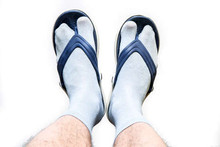 The hairy man legs with socks and flip flops on the feet. Symbol for bad taste or fashion style.
