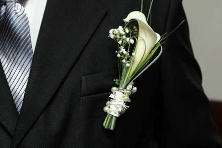 A detail picture of the groom's flower pinned on the suit. A traditional decoration for the wedding.
