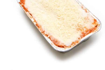 The semifinished lasagna in the aluminum tub isolated on a white background. The fast ready to cook meal. 免版税图像