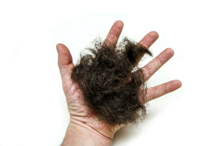 The hand of a man with a palm full of the hair. Symbol for the haircutting or hair loss.