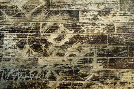 The detail of the old worn out wooden bench with a lot of carvings from the people.
