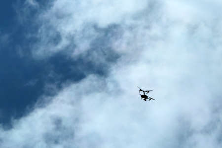 The small drone flying high pictured against the cloudy sky. Only the silhouette is visible.