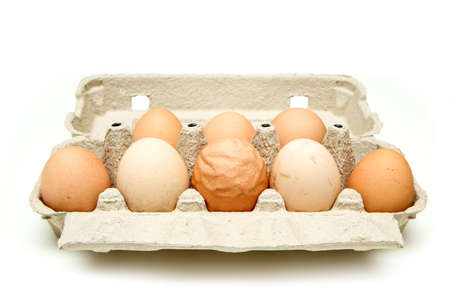 The organic egg with rough and wavy eggshell among other good eggs. Isolated on white background. Reason can be the old hen, insufficient nutrition or wrong process of formation of the egg.