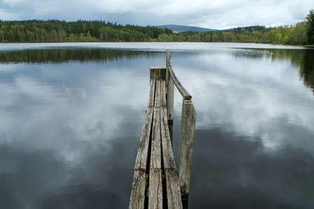 The old wooden pier over the surface of the pond in Czech nature during the cloudy day with a fine rain.