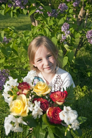 happy girl holding flowers in sun-setting light in the garden photo
