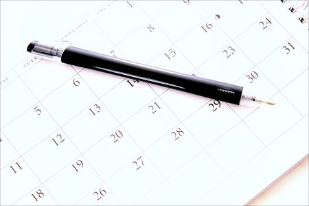 black pen laying on calander Imagens