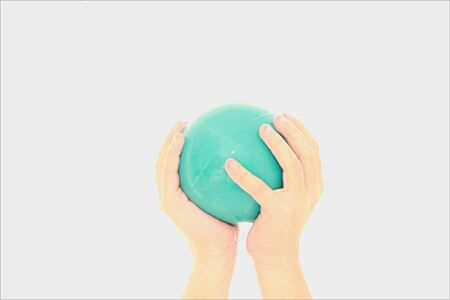 childs hand holding ball