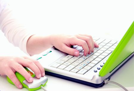 childs hands on computer keyboard and mouse photo
