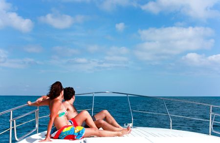 Lifestyles. Man and woman sunbathing on the bow of a motor boat in the sea. photo