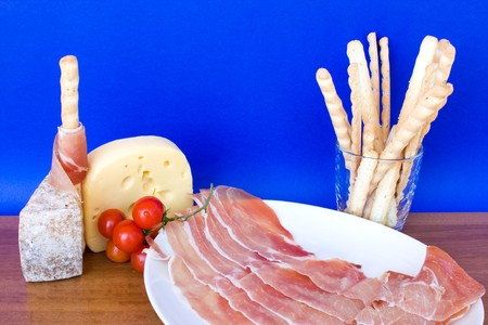 cherry tomatoes: Food & Drinks -  italian appetizers: ham, cheese, bread-sticks and cherry tomatoes. Stock Photo