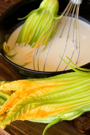 Food And Drinks - Italian Food - Closeup of bowl with batter for the fried zucchini flowers preparation. Stock Photo