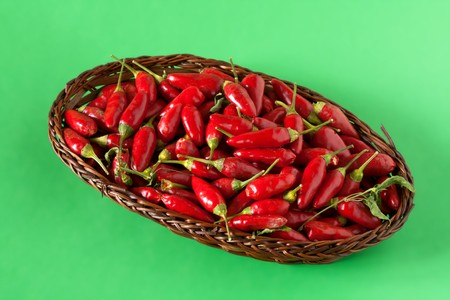 Small basket with chili peppers isolated on green background. Stock Photo - 7965045