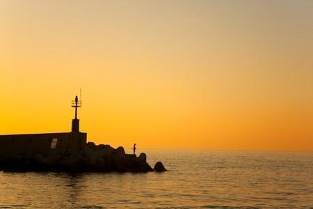 Silhouette of fisherman at sunset, Marciana Marina, Elba Island, Italy. photo