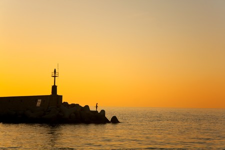 Silhouette of fisherman at sunset, Marciana Marina, Elba Island, Italy.