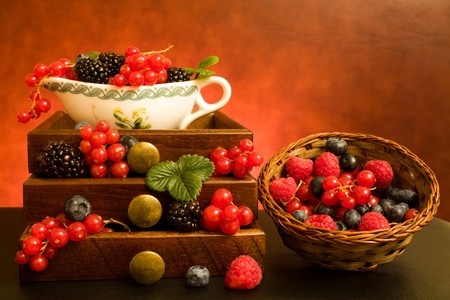 Still life with soft fruits in wooden drawers and basket. photo