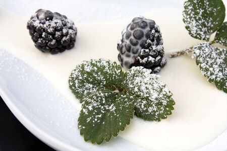 Desserts - Closeup of plate with blackberries, cream and icing sugar. photo