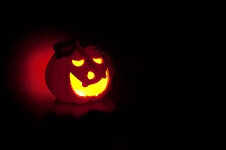 Illuminated Halloween pumpkin on black background. photo