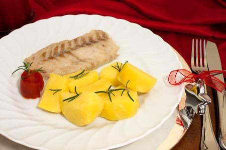 Food - Plate with fish and potatoes on Christmas table. photo