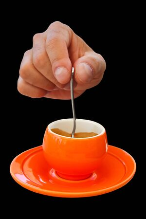 coffee hour: Drinks - Coffee - Hand with spoon and coffee cup isolated on black background. Stock Photo