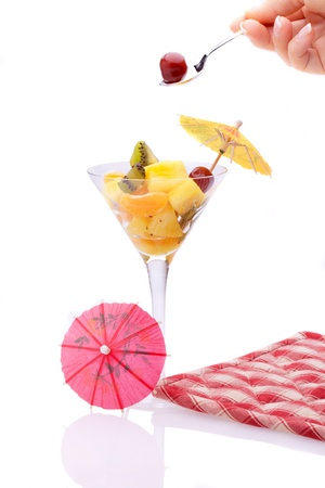 Cherry From Fruit Salad - Food - Desserts - Cup with fruit salad decorated with paper umbrellas and hand holding teaspoon with a cherry, isolated on white background. photo