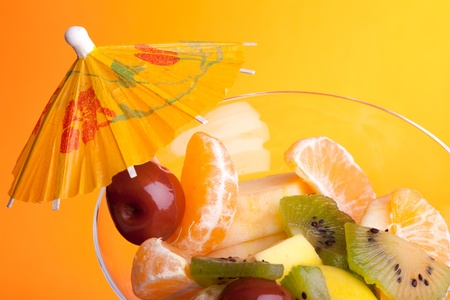 Food - Desserts - Cup with fruit salad decorated with paper umbrella, isolated on orange background.