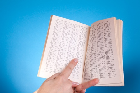 university word: Hand With Dictionary - Educational - Hand holding an opened dictionary book. Stock Photo