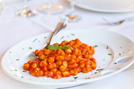 Made by restaurants around the world, this homemade gnocchi recipe is one of the most popular Italian first course dishes. An easy preparation and taste of fresh tomato sauce, combined with scent freshness of basil and mozzarella. photo
