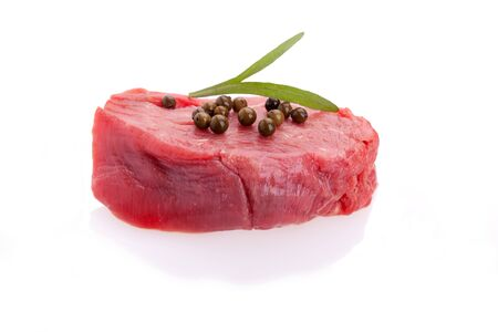 Raw tenderloin decorated with green pepper and tarragon on white background. photo