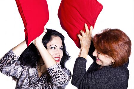 women fighting: Two women fighting with pillows. Stock Photo