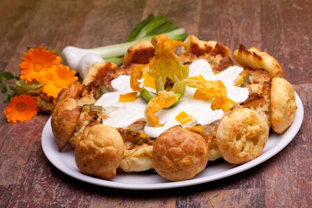 International Cuisine - French Recipes - Gougère cake with vegetables decorated with mozzarella, zucchini flower and small choux. photo