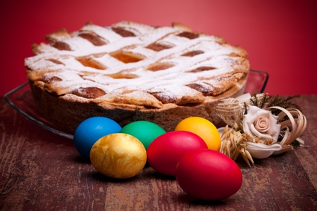 International Cuisine - Desserts - Neapolitan Pastiera and colorful Easter eggs. Pastiera is a wheat and ricotta pie that is also known as Pizza Gran. Archivio Fotografico