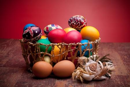 Cesta con coloridos huevos de Pascua en fondo rojo. photo