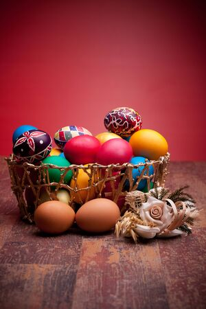 Basket with colorful Easter eggs on red background. photo